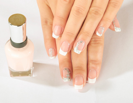french manicure: beautiful female hands with French manicure with varnish bottle