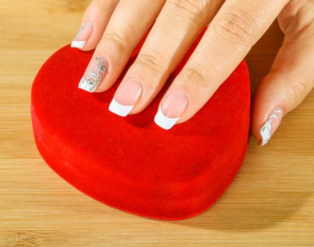 beautiful female hands with manicure holding a box of heart-shaped photo