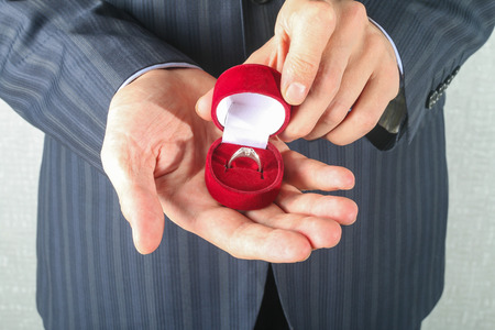 Close up of man holding engagement ring and gift box photo