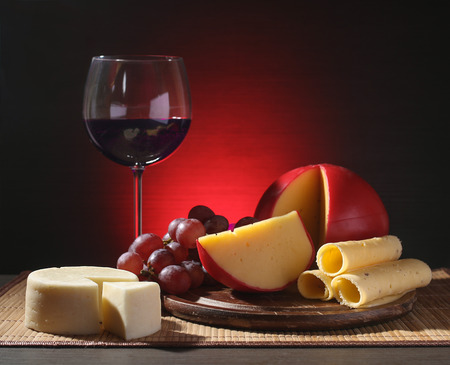 amorousness: Refined still life of wine, cheese and grapes on wooden table on lightening background