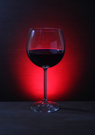 romantic evening with wine: Close up on Glass of Red Wine with Lights Background Stock Photo