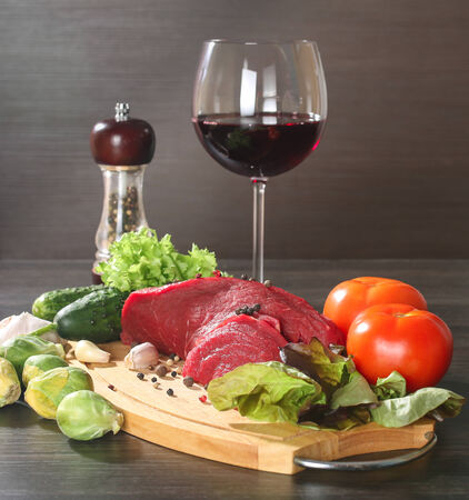 Raw beef meat with vegetables and wine on wooden table photo
