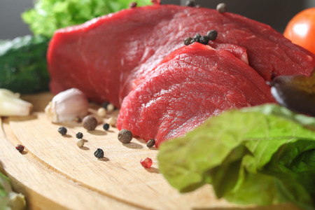 Raw beef meat with vegetables on wooden table close up photo