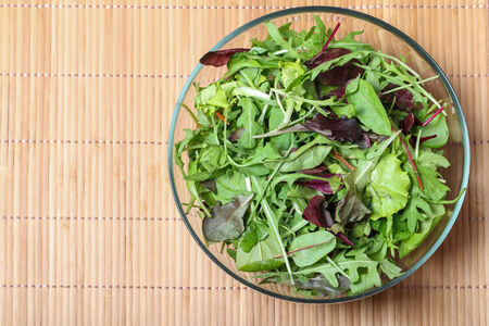 rocket lettuce: Fresh green salad with spinach,arugula,rom aine and lettuce on bamboo background