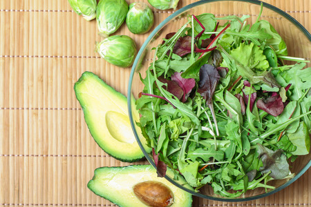 rocket lettuce: Fresh green salad with spinach,arugula,rom aine and broccoli and avocado on bamboo background