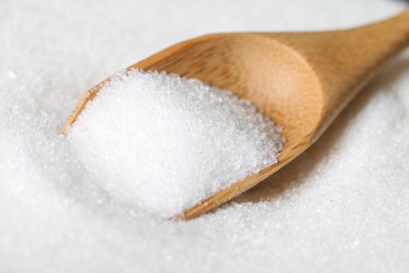 White sugar in a wooden spoon. Selective focus