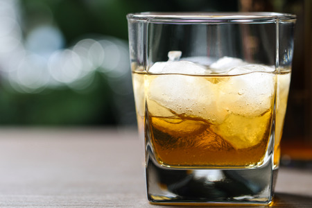 glass with whiskey and ice on wooden table on the background of trees photo