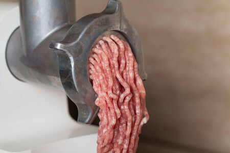 Mincer with raw chopped meat in plate photo