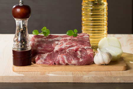 Fresh raw pork on light wooden cutting board with onion, garlic, pepper and vegetable oil photo