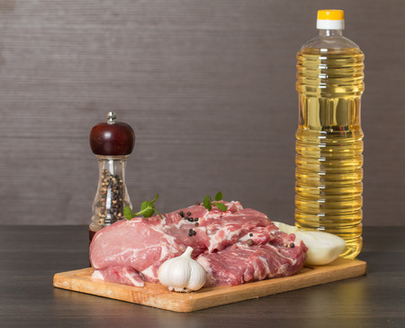 vegetable oil: Fresh raw pork on light wooden cutting board with onion, garlic, pepper and vegetable oil