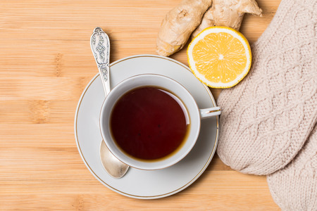 Cup of tea with honey,  ginger and lemon on wooden table photo