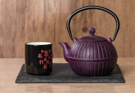 stand teapot: Chinese traditional teapot and cup on wooden background Stock Photo