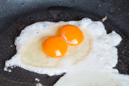 scrambled: Close-up photo of two scrambled eggs in black frying pan