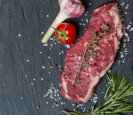 australian beef cow: Raw meat steak with fresh herbs and salt on a stone black background Stock Photo