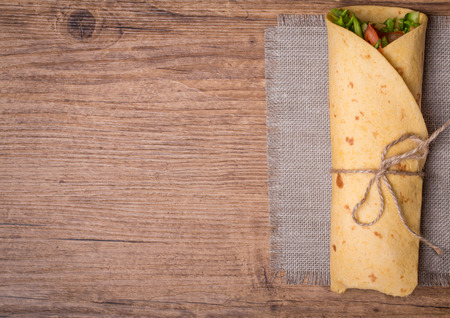 breakfast plate: fresh tortilla wraps with vegetables on wooden background top view