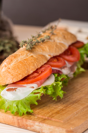 crusty french bread: Ham and cheese salad submarine sandwich from fresh baguette on wooden background