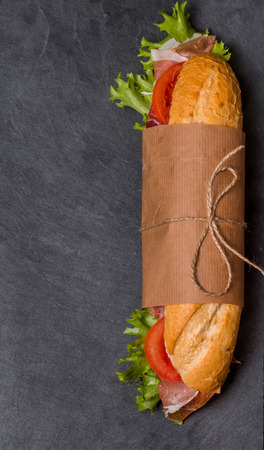 crusty french bread: Ham and cheese salad submarine sandwich from fresh baguette on black background