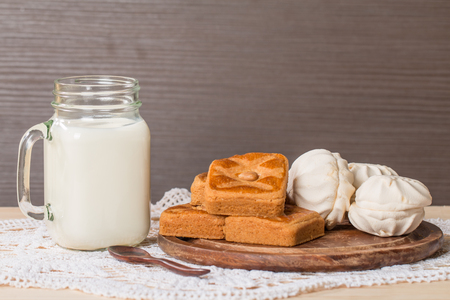 Fresh milk in glass and sweet cookies with zephyr on wooden background photo