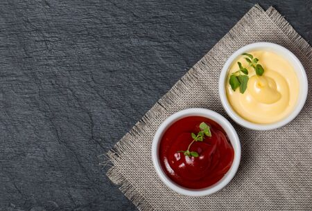 sweet mustard: ketchup and mayonnaise - two kinds of sauces on black background top view