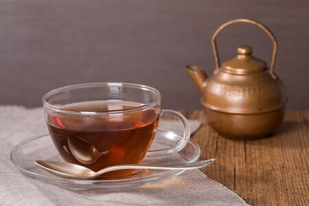 Cup of tea and a vintage teapot on wooden background photo