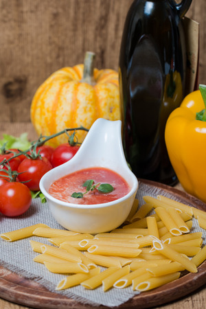 italian cusine: Tomato sauce in a white sauce boat with fresh ingredients and pasta Stock Photo