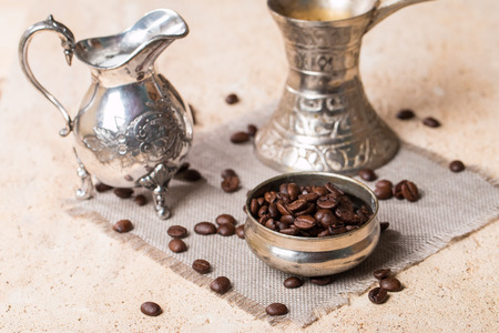 the milk jug: coffee beans in bowl milk jug and coffee pot on stone background