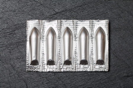 suppositories: Silver package of suppository on black background