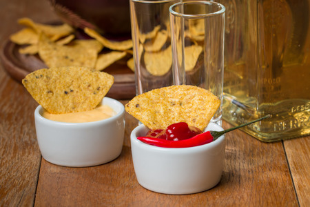 nacho: Mexican nacho chips, cheese and salsa dip in bowl and tequila on wooden background Stock Photo