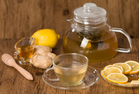 Glass cup of ginger tea with honey and lemon on wooden table photo