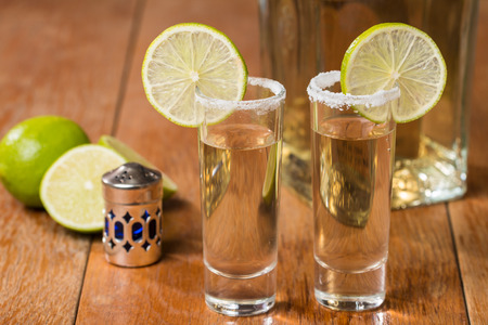 Gold Tequila in Shot Glasses with Lime and Salt on wooden background photo