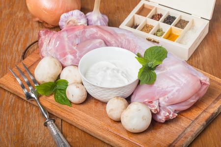 Rabbit carcass,  garlic, onion, sour cream, mushrooms and spices on wooden cutting Board Reklamní fotografie