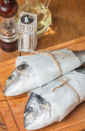 dorado fish: Fresh dorado fish cooking with spices and condiments on wooden table Stock Photo
