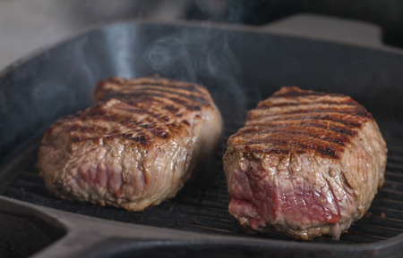 grill: Hot Grilled beef steaks are cooking on grill pan