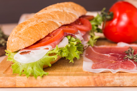Ham and cheese salad submarine sandwich from fresh baguette on wooden background photo