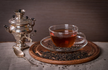 Cup of tea and small samovar on wooden background photo