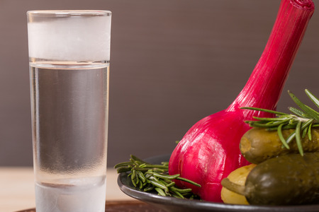 feed the poor: shot of vodka with pickles cucumber and garlic on wooden table Stock Photo