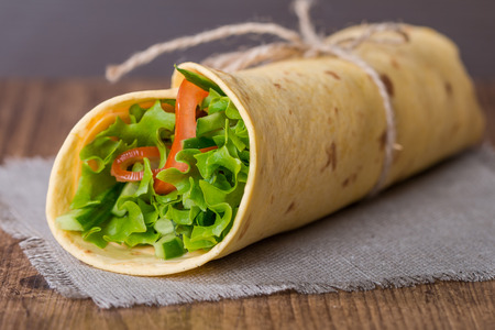 tortilla wrap: fresh tortilla wrap with vegetables on wooden background