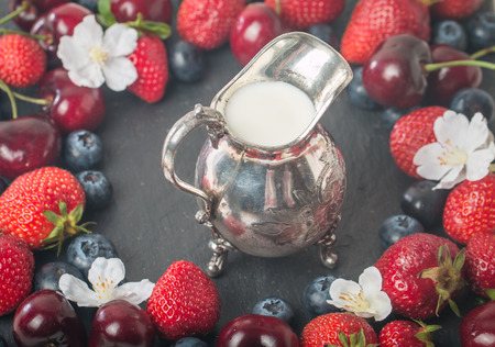 creamer: frame of fresh berries with creamer on black stone background