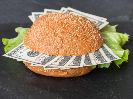 hamburger: Hamburger with dollar bank notes on black background Stock Photo