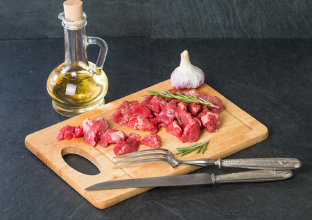 beefsteak: Raw beef cubes with rosemary and beefsteak spices on wooden cutting Board Stock Photo