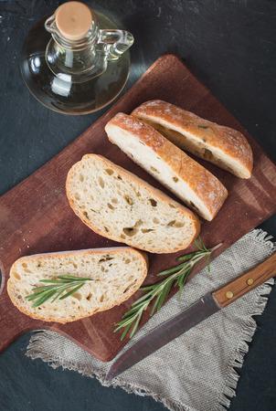 ciabatta: Sliced bread Ciabatta and rosemary on black background, top view
