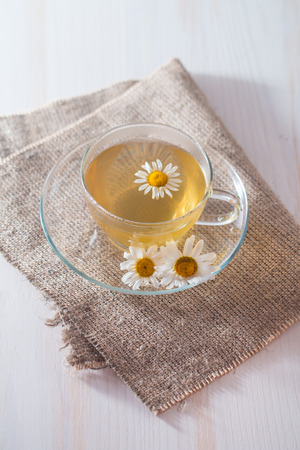 flap: cup of chamomile tea with chamomile flowers on flap of burlap