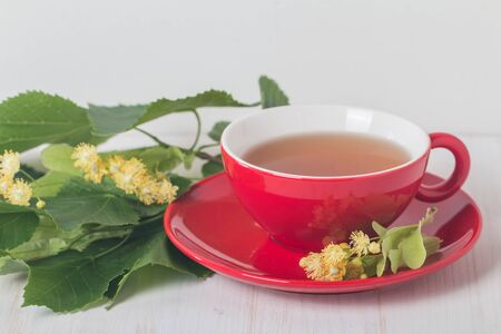 stimulated: Red cup of linden tea  on white wooden background Stock Photo