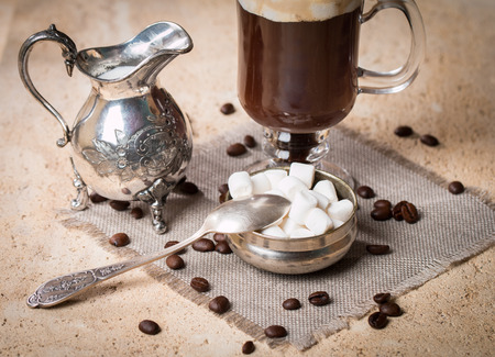 the milk jug: marshmallow, milk jug, spoon and Glass Cup of coffee  on stone background