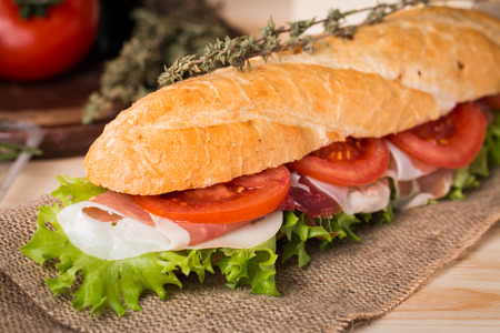 crusty french bread: Ham and cheese salad submarine sandwich from fresh baguette on burlap Stock Photo
