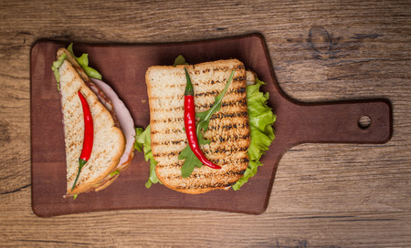 sandwich bread: Classic club sandwich with bacon and vegetables on wooden chopping board top view Stock Photo
