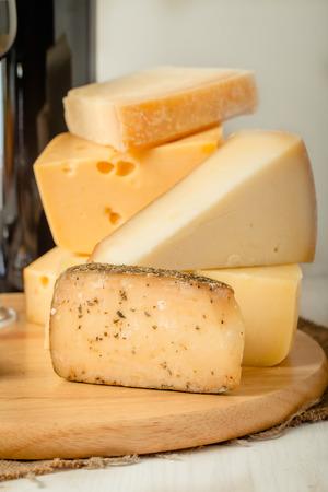 queso de cabra: Placa del queso Surtido con vino tinto, las nueces y la miel en el fondo de madera blanca