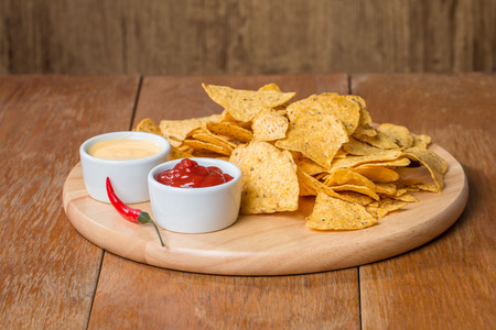 mexican food: nachos with various sauces on wooden table