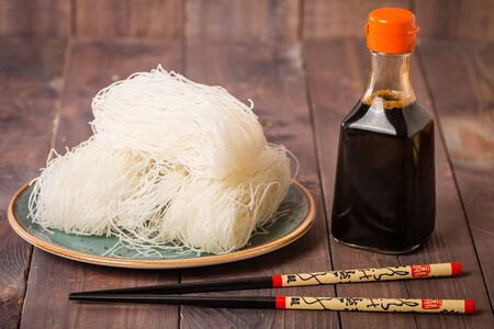 sauce bottle: Asian raw glass noodles, chopsticks and soy sauce on wooden background