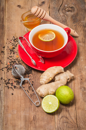 chinese herbs: Cup of tea with ginger,  honey and lemon on wooden table Stock Photo